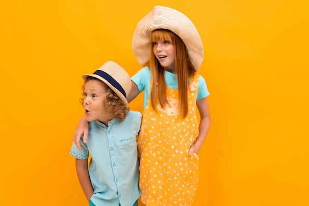 Dwoje zaskoczonych rudowłosych przyjaciół patrzy w letnie kapelusze, patrząc w bok