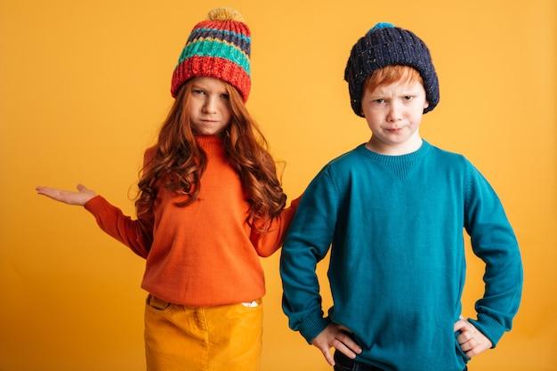 Dwoje zdezorientowanych małych rudych dzieci w ciepłych kapeluszach.