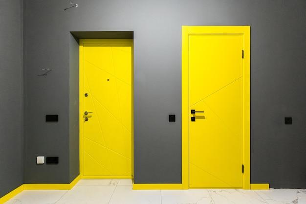 Dwoje żółtych drzwi z czarnymi uchwytami na szarej ścianie