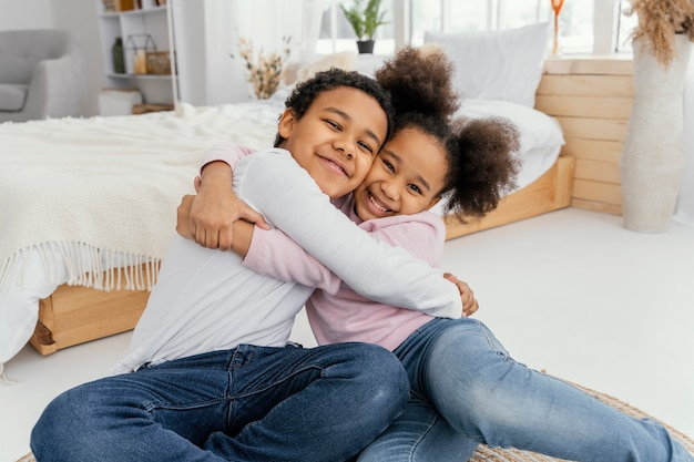 Dwójka rodzeństwa obejmująca się w domu
