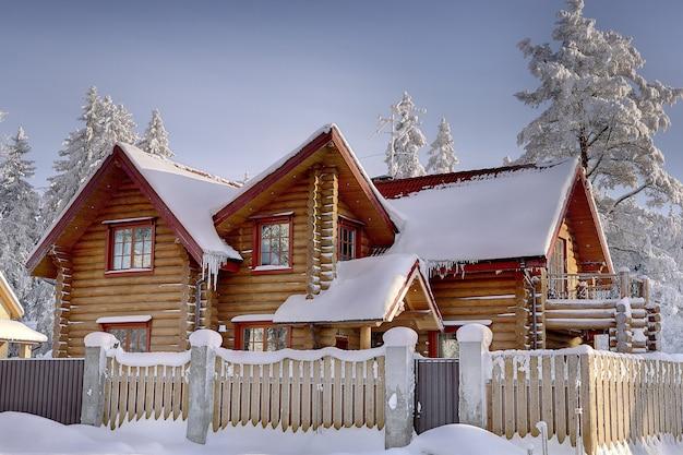 Dworek z bejcowanych bali, otoczony drewnianym płotem w śnieżnym zimowym lesie.