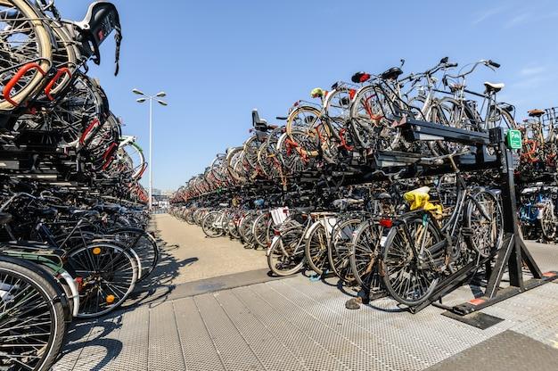 Dworzec centralny w amsterdamie. wiele rowerów zaparkowanych przed dworcem głównym