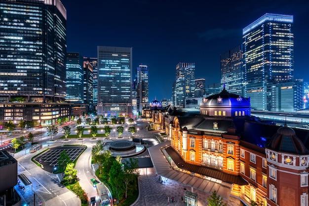 Dworzec kolejowy w tokio i budynek dzielnicy biznesowej w nocy, japonia.