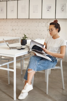 Dwudziestokilkuletnia kobieta robi karierę w projektowaniu mody, patrząc na magazyn siedzący w swoim jasnym studio z laptopem.