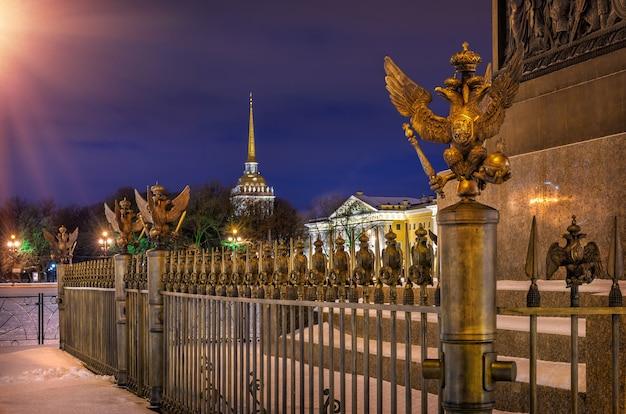 Dwugłowe orły na siatce przy filarach aleksandra na placu pałacowym w petersburgu i admiralicja z dala w nocnym świetle