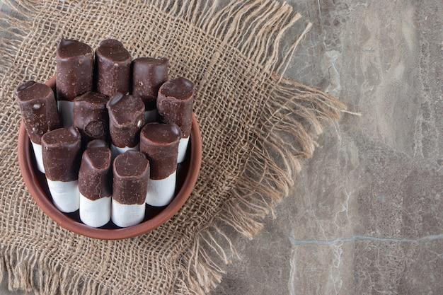 Dwukolorowe cukierki w misce na fakturze na niebiesko.