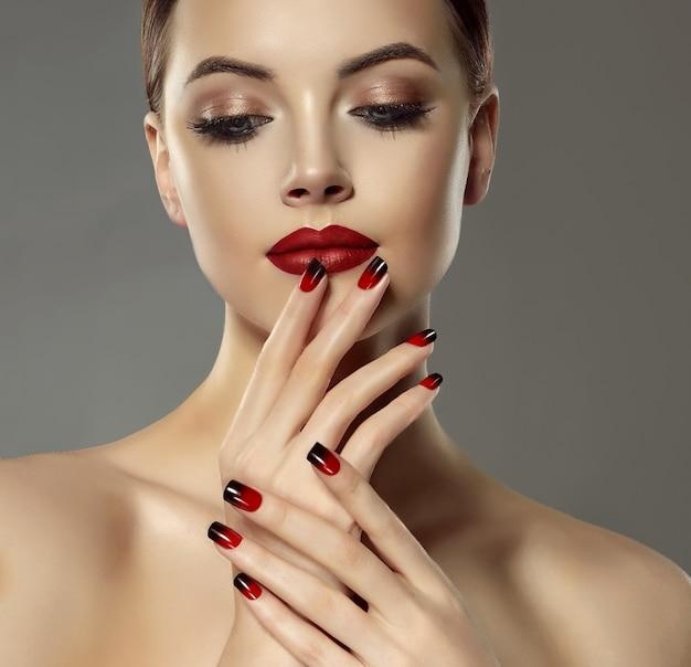 Dwukolorowy manicure na smukłych palcach przepięknej modelki, dotyka czerwonych ust. piękno i wdzięk. bliska portret kobiety w stylowy makijaż. makijaż mody i kosmetyki.