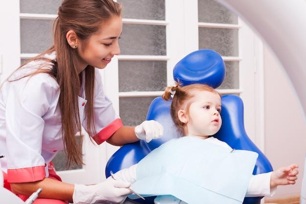 Dwuletnia dziewczynka jest na pierwszej wizycie w gabinecie stomatologicznym. młoda atrakcyjna kobieta dentysta