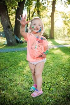 Dwuletnia dziewczynka poplamiona kolorami na zielonym trawniku