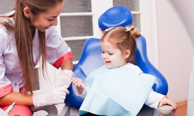 Dwuletnia dziewczynka uczy się myć zęby szczoteczką w ręku w gabinecie stomatologicznym