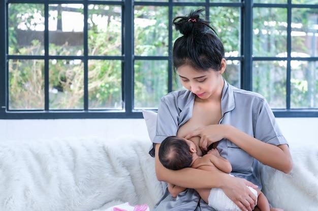 Dwumiesięczne azjatyckie dziecko jest szczęśliwe, że może ssać mleko matki.
