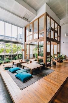 Dwuosobowa sala ozdobiona drewnem wewnątrz ogólnodostępnego hostelu z niskimi stolikami, workami z fasolą i poduszkami.