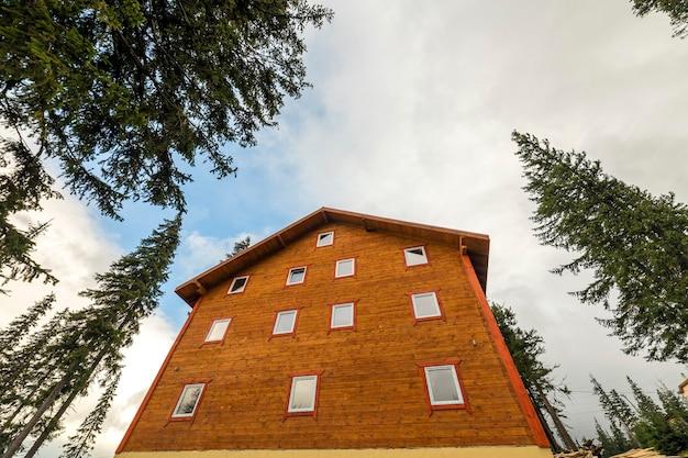 Dwupiętrowy drewniany domek z desek i bali na niebieskim niebie