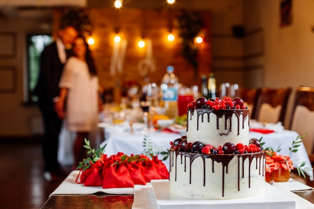 Dwupoziomowy biały tort weselny, ozdobiony świeżymi czerwonymi owocami i jagodami, oblany czekoladą