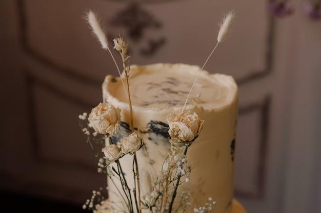 Dwupoziomowy tort ozdobiony suszonymi kwiatami w stylu boho