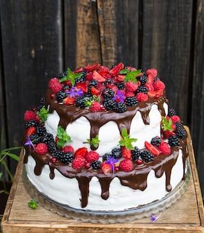 Dwupoziomowy tort z owocami i kwiatami. deser. ciasto z czarnego lasu