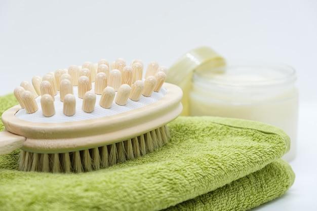 Dwustronna szczotka masująca do mycia ciała leży na ręczniku na tle peelingu do ciała