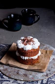 Dwuwarstwowy deser z białą śmietaną zwieńczoną startą czekoladą