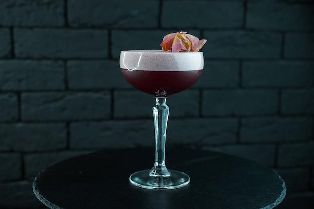 Dwuwarstwowy pyszny słodki koktajl z czerwonej żurawiny z tonikiem i wódką z likierem jagodowym z pianką stoi na stole na czarnym tle. oryginalne koktajle alkoholowe. weekend w barze