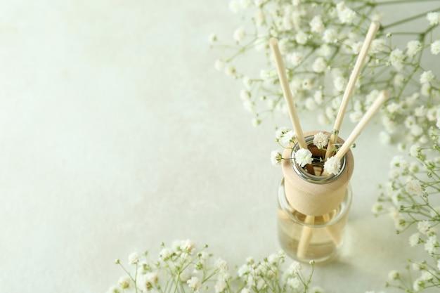 Dyfuzor i kwiaty na białym teksturowanym stole