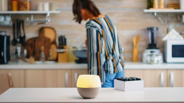 Dyfuzor olejków eterycznych rozprowadzający aromaterapię, gdy kobieta spaceruje po kuchni. aroma esencja zdrowotna, welness aromaterapia domowe spa zapach spokojna terapia, para terapeutyczna, zdrowie psychiczne tr