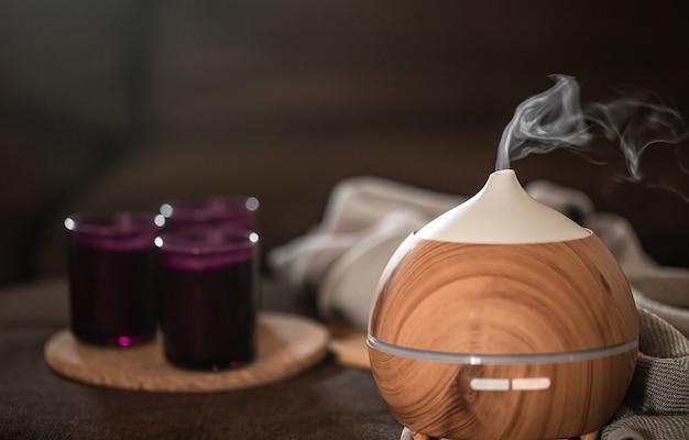 Dyfuzor oleju na rozmytym tle z elementami dekoracyjnymi. koncepcja aromaterapii i opieki zdrowotnej.