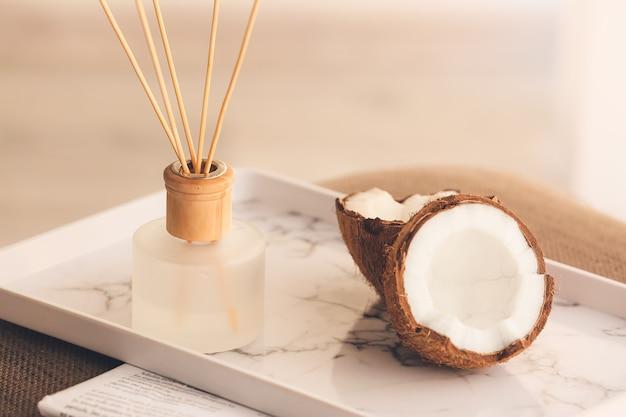 Dyfuzor trzcinowy i kokos na stole w pokoju