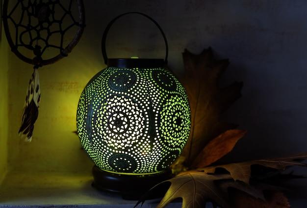 Dyfuzor zapachowy w stylu antycznej lampy orientalnej. martwa natura z dyfuzorem, łapaczem snów i liśćmi klonu.