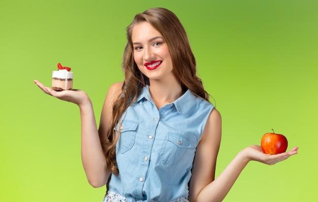 Dylemat. kobieta na diecie. niezdecydowana kobieta z jabłkiem i babeczką