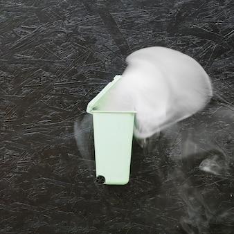 Dym wychodzi z miniaturowego zielonego kosza na śmieci