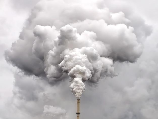 Dym z fajki fabrycznej na tle ciemnego zachmurzonego nieba