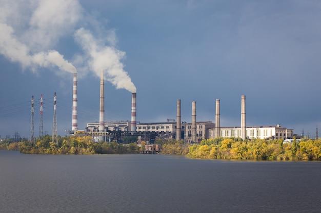 Dym z komina elektrowni na moście nad rzeką