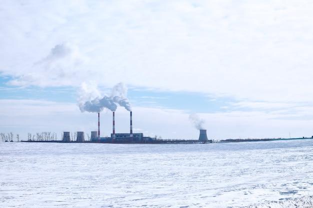 Dymiące kominy fabryki na tle błękitnego nieba z chmurami i białym śniegiem