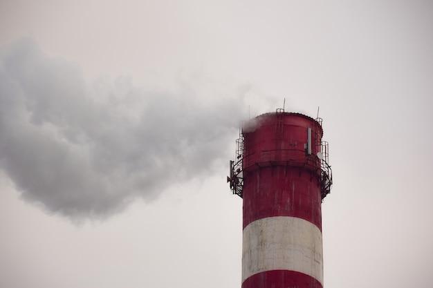 Dymiący komin fabryki lub fabryki na tle nieba