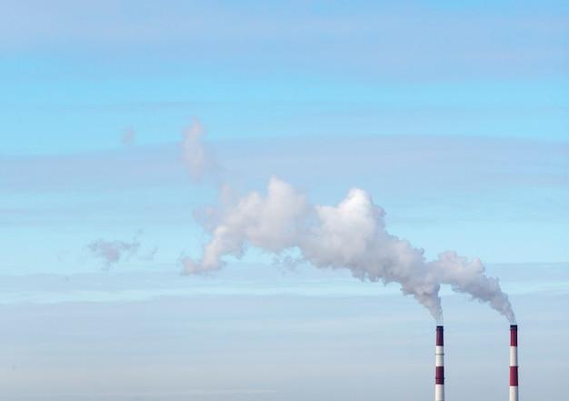 Dymiący kominy z niebieskim niebem