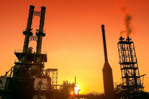 Dymne stosy przemysłu petrochemicznego na zachód słońca pomarańczowego nieba, zakładu przemysłowego ropy i gazu