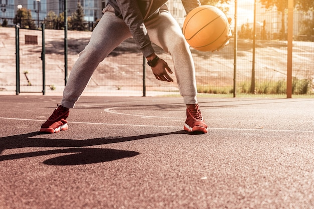 Dynamiczna gra. miły młody człowiek trzyma piłkę do koszykówki podczas grania w grę