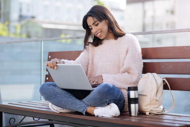 Dynamiczna, pozytywna młoda kobieta, pisząca wiadomość do swojej przyjaciółki, siedząc na ławce i ciesząc się ciepłym dniem na zewnątrz
