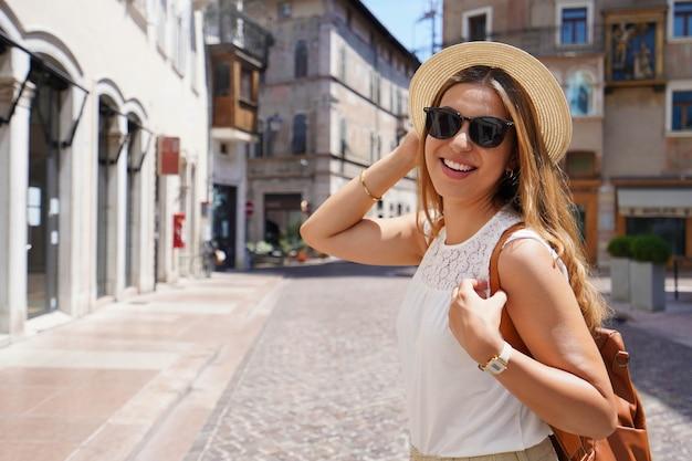 Dynamiczna wesoła kobieta na kulturalnym miejscu przeznaczenia w europie. moda dziewczyna patrząc na kamery na jej turystyczne przygody. skopiuj miejsce.
