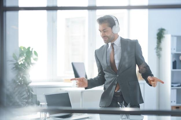 Dynamiczny biznesmen w słuchawkach i formalnej odzieży stojącej przy biurku i tańczący przy przerwie