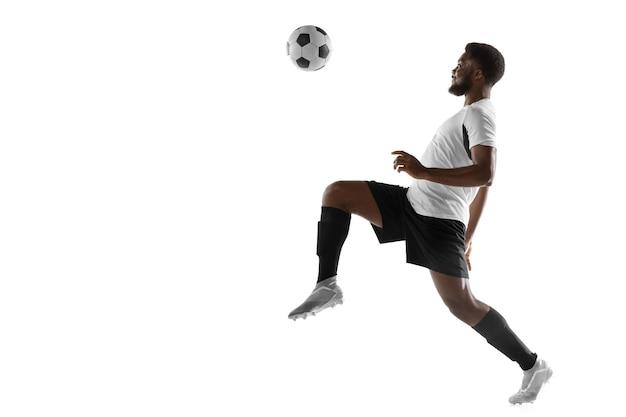 Dynamiczny. młody człowiek afryki, mężczyzna piłka nożna piłkarz szkolenia na białym tle.