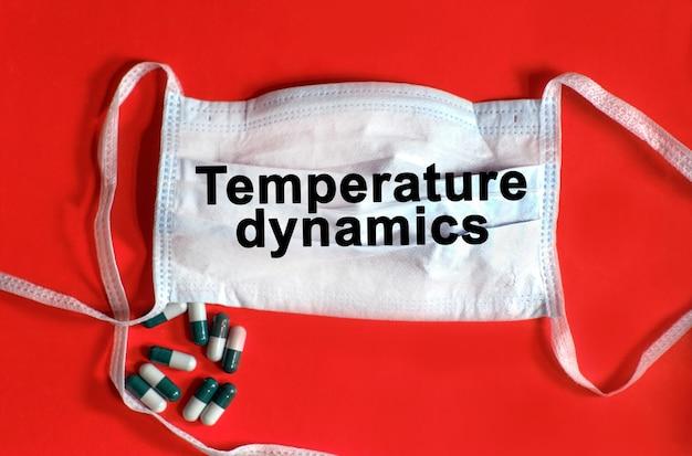 Dynamika temperatury - tekst na masce ochronnej, tabletki na czerwonym tle