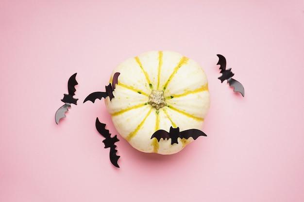 Dynia halloween i nietoperze na różowym tle, leżał płasko.