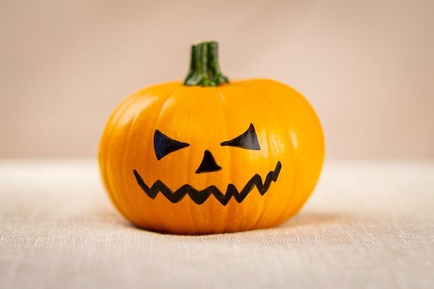 Dynia halloween z pomalowaną czarną twarzą.