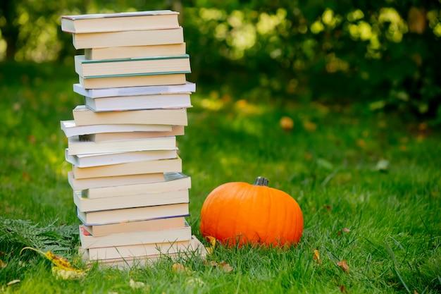 Dynia i książki są na zielonej trawie w ogrodzie