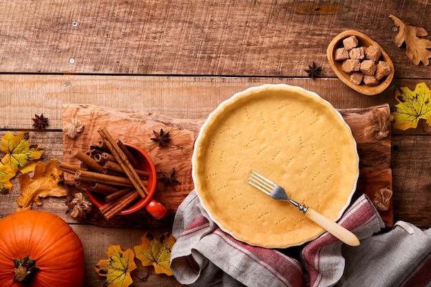 Dynia i składniki żywności, przyprawy, cynamon i naczynie kuchenne na stare rustykalne drewniane tła. koncepcja domowych wypieków na wakacje. gotowanie ciasta z dyni i ciasteczek na święto dziękczynienia.