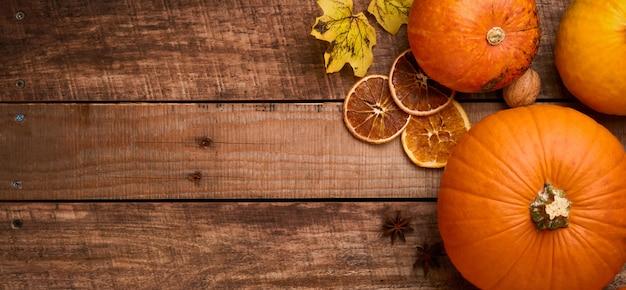 Dynia. jesienne tło jedzenie z cynamonem, orzechami i sezonowymi przyprawami na tle rustykalnym. gotowanie szarlotki lub dyni i ciasteczek na święto dziękczynienia i jesienne święta. widok z góry z miejsca na kopię.