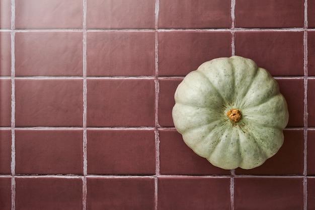 Dynia. jesienne tło żywności z cynamonem, orzechami i sezonowymi przyprawami na tle starych płytek ceramicznych. gotowanie szarlotki lub dyni i ciasteczek na święto dziękczynienia i jesienne święta. widok z góry.