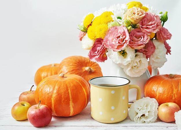 Dynia jesiennych zbiorów. dynie, jabłka i kwiaty na stole. stół dziękczynienia. skopiuj miejsce. halloween lub sezonowe jesienne. kartka z życzeniami. kuchnia jesienna.