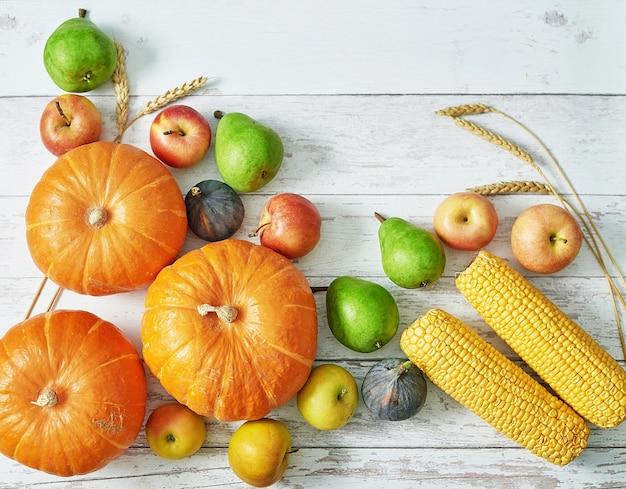 Dynia jesiennych zbiorów. jesienne zbiory warzyw i owoców. dynie, jabłka, gruszki, kukurydza na stole. stół święto dziękczynienia. halloween lub sezonowa jesień. kartka z życzeniami. kuchnia jesienna.